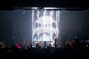 LED Cage live on stage with Camo & Krooked at a Hospitality event. Showing image of Skeletor.