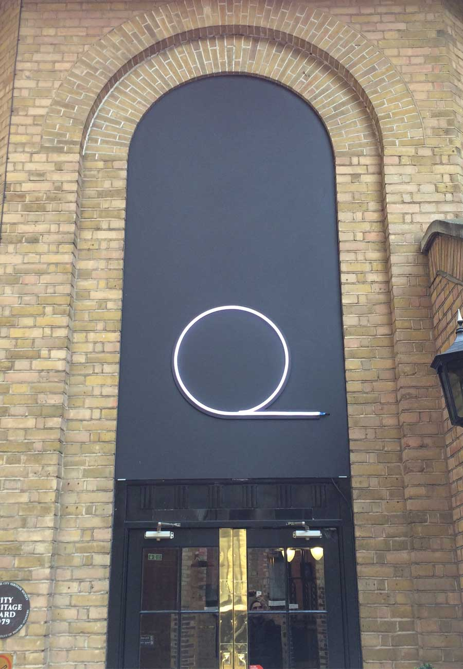 Quantcast logo in LED neon sign over a doorway
